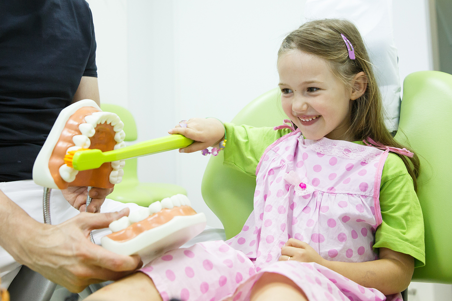 Smiling little girl in dentists chair being educated about proper tooth-brushing by her paediatric dentist. Early prevention raising awareness oral hygiene demonstration concept.