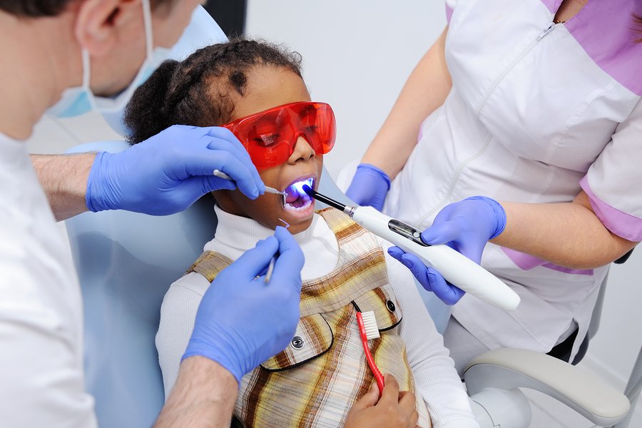 young girl at the dentist receiving dental laser treatment for a cavity