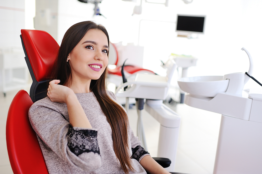 pretty woman in dental chair waiting for teeth whitening process
