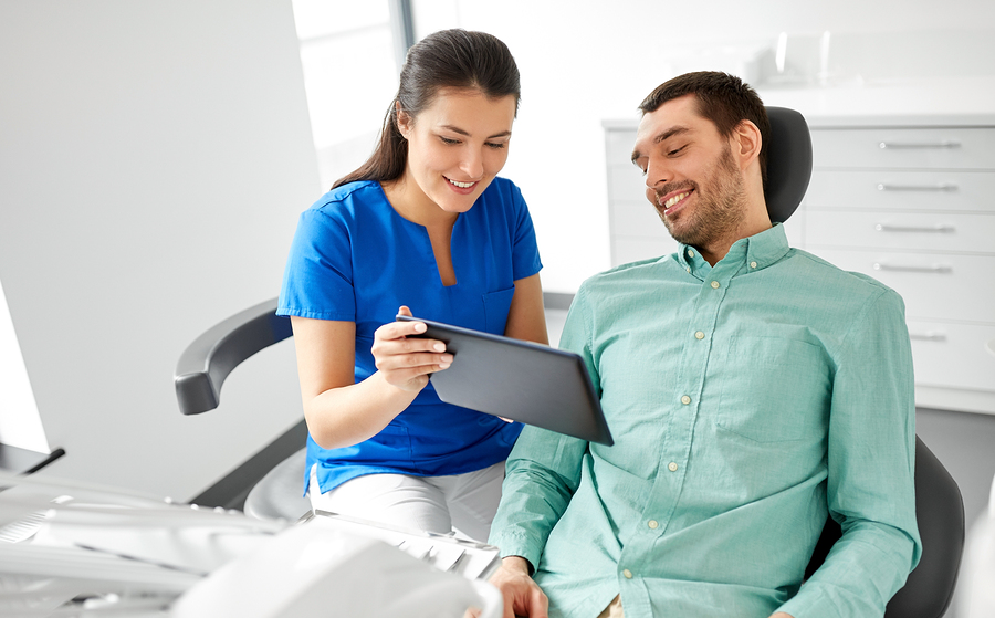 smiling young man in dentist chair looking at dentist's tablet computer as she explains a dental procedure