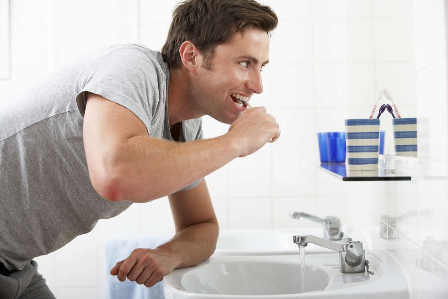Man In Bathroom leaning on sink and brushing his teeth to maintain healthly gums and teeth
